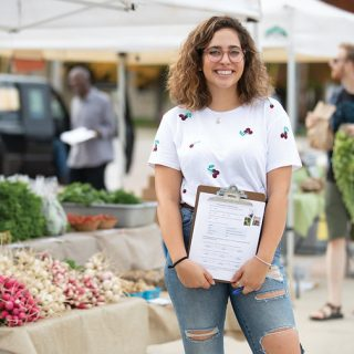 student in front of farmers market